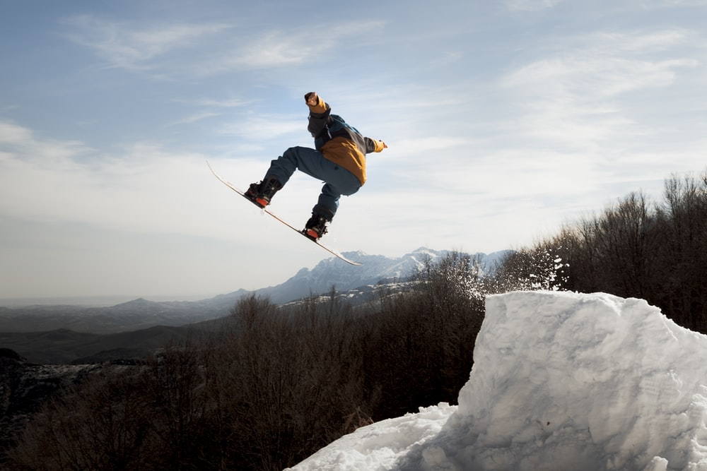 man in blue jacket and black pants riding ski blades on snow covered mountain during daytime