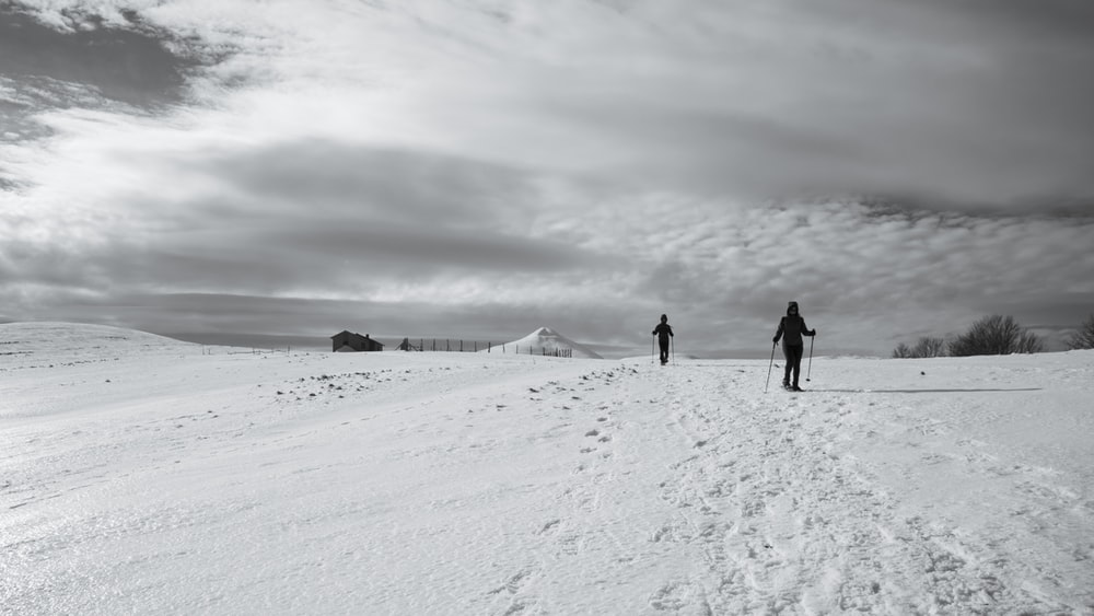 2 person walking on snow covered ground during daytime