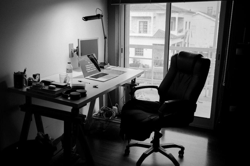 black office rolling chair near white wooden desk