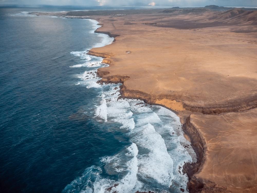aerial view of ocean waves crashing on shore during daytime