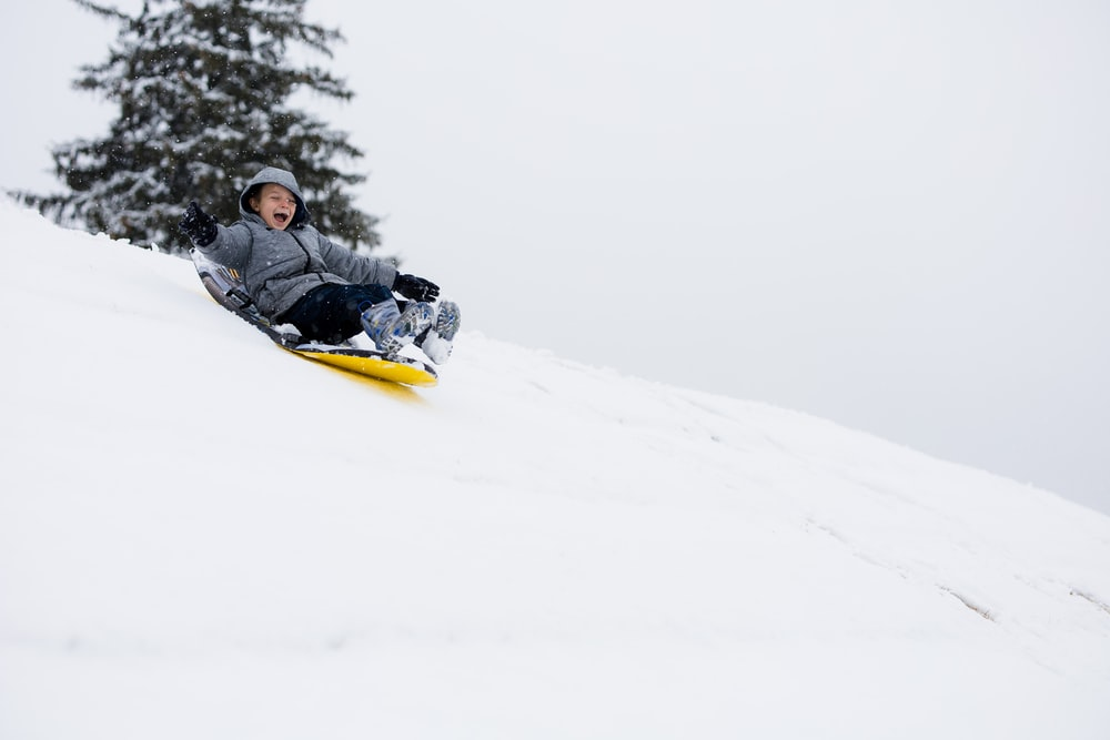 man in black jacket riding yellow snow sled on snow covered ground during daytime