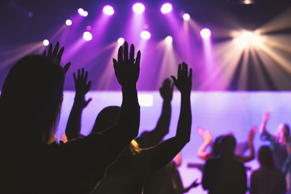 people raising their hands in front of a concert