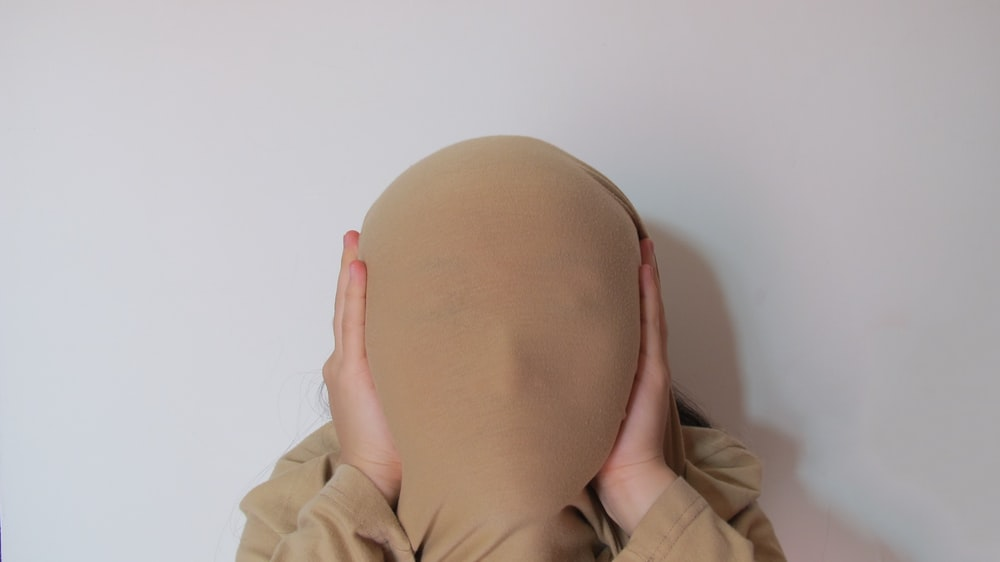 person in beige jacket holding brown egg