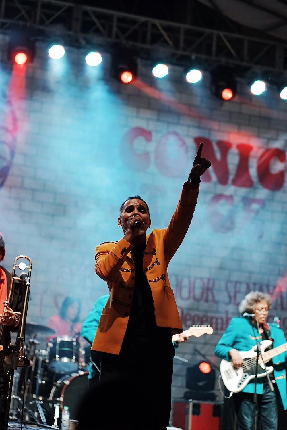 man in brown coat singing on stage