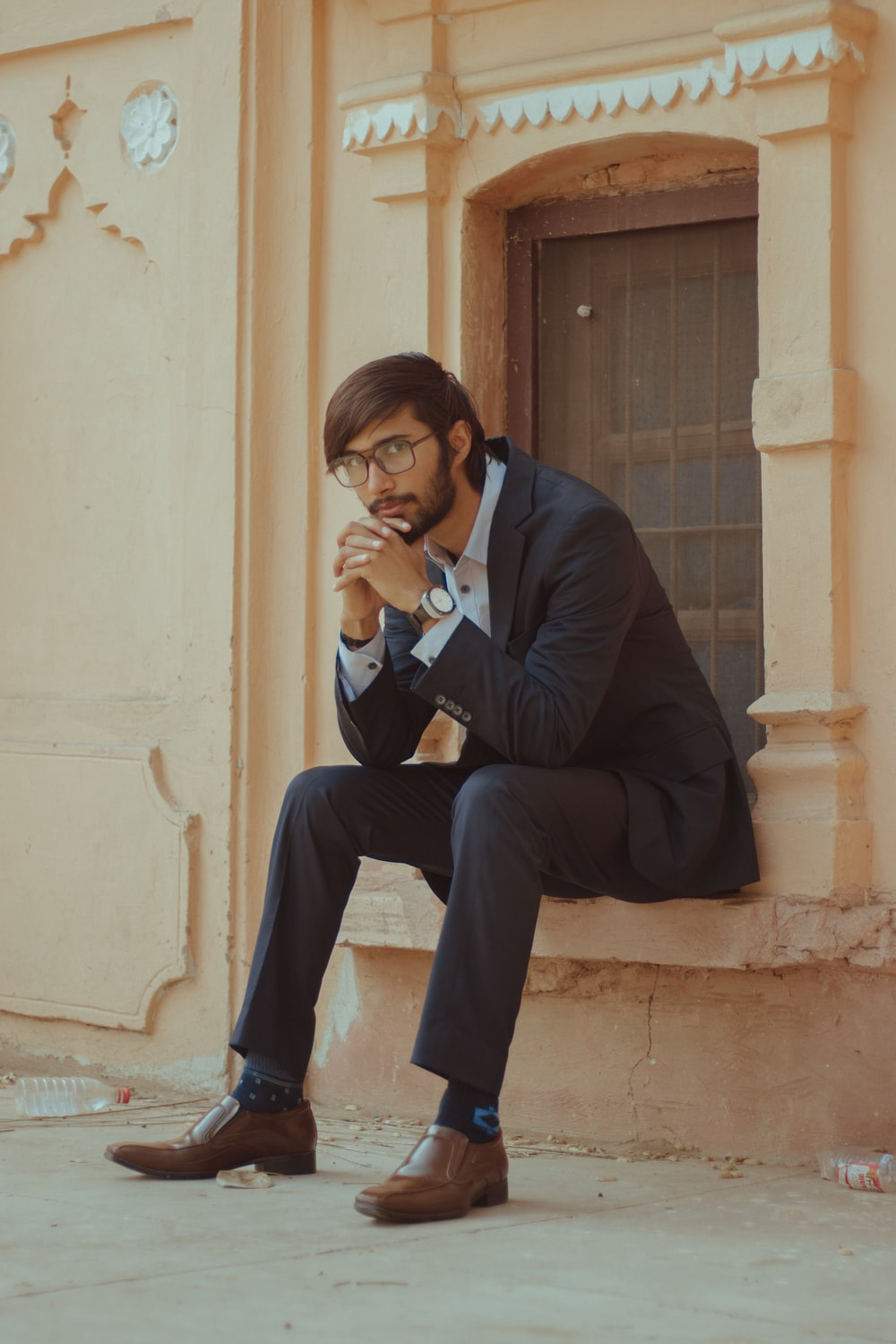 man in black suit jacket and black pants sitting on concrete bench