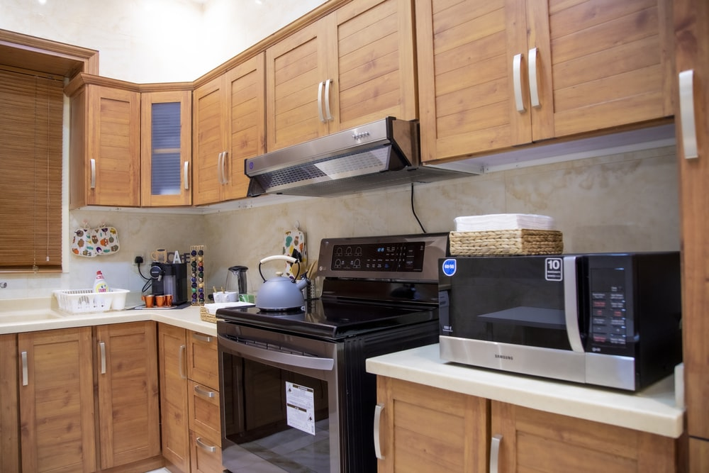 white microwave oven on brown wooden kitchen cabinet