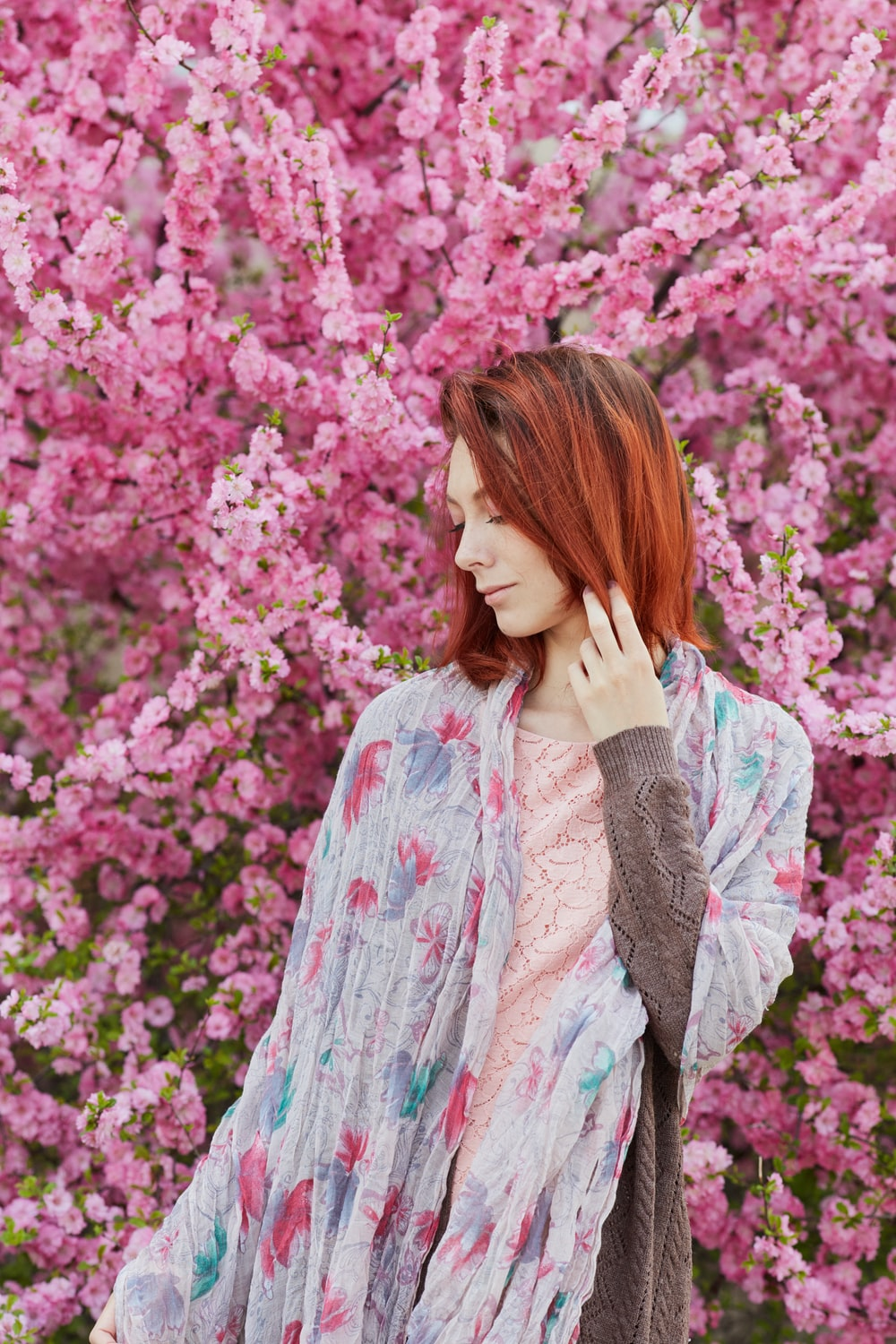 woman in white and blue long sleeve shirt standing near pink flowers