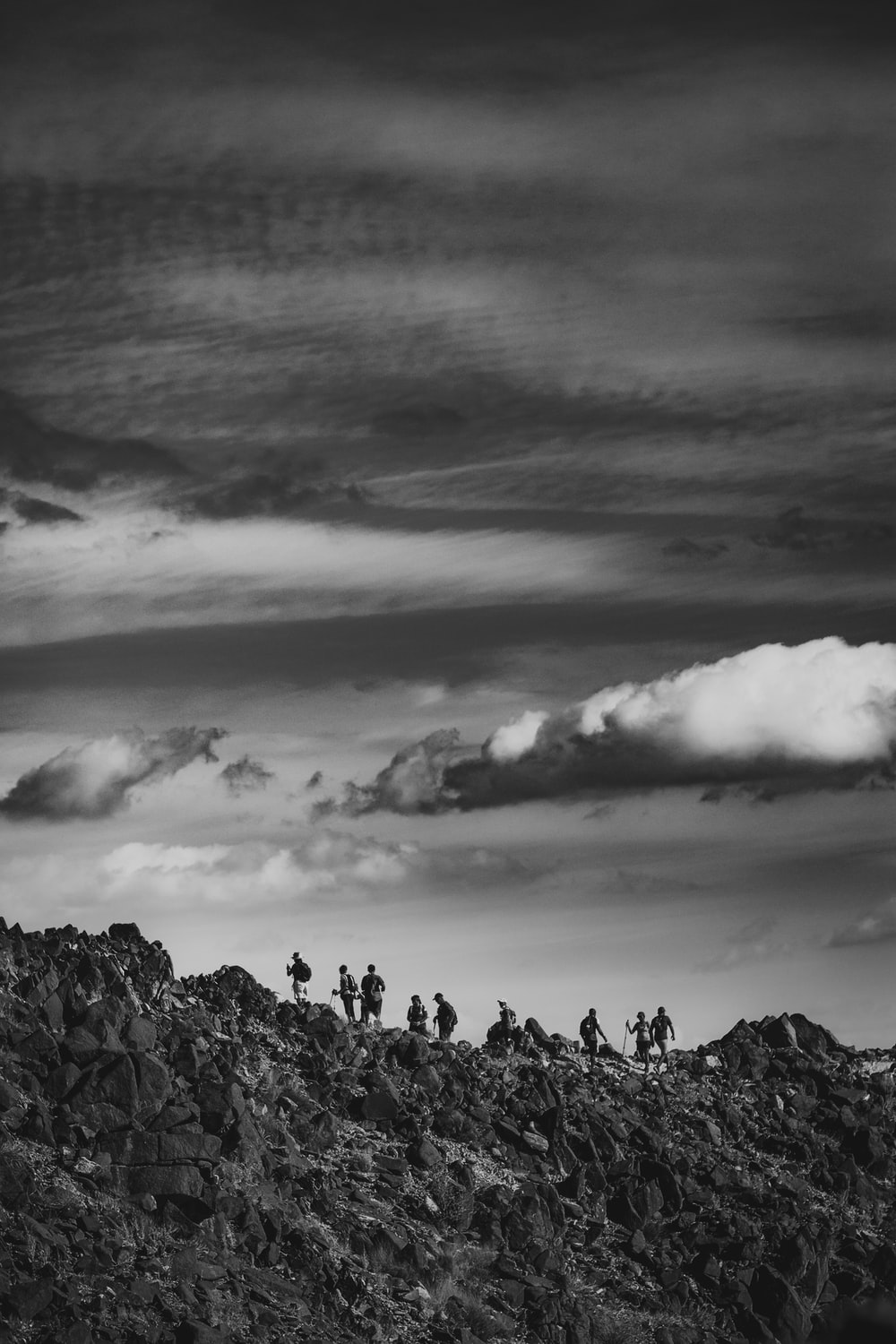 grayscale photo of people on rocky mountain under cloudy sky