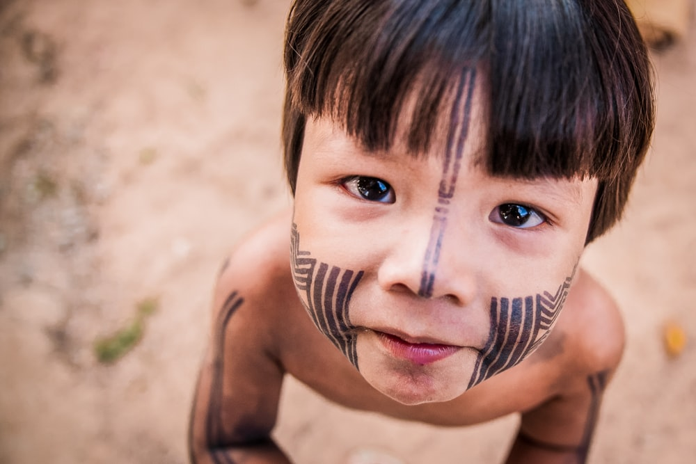 topless boy with black and white face paint
