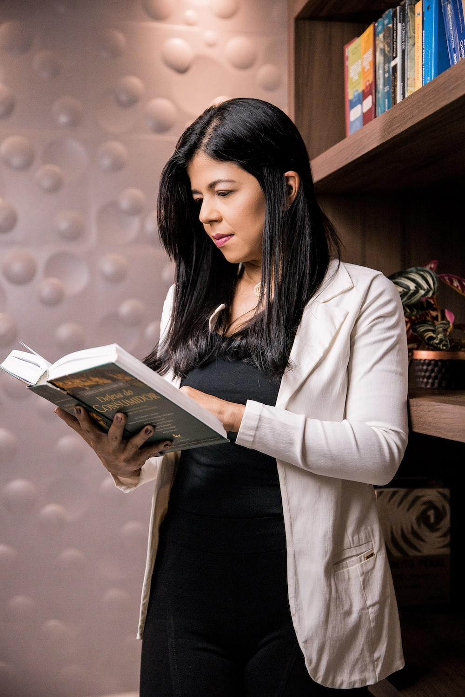 woman in white blazer holding book
