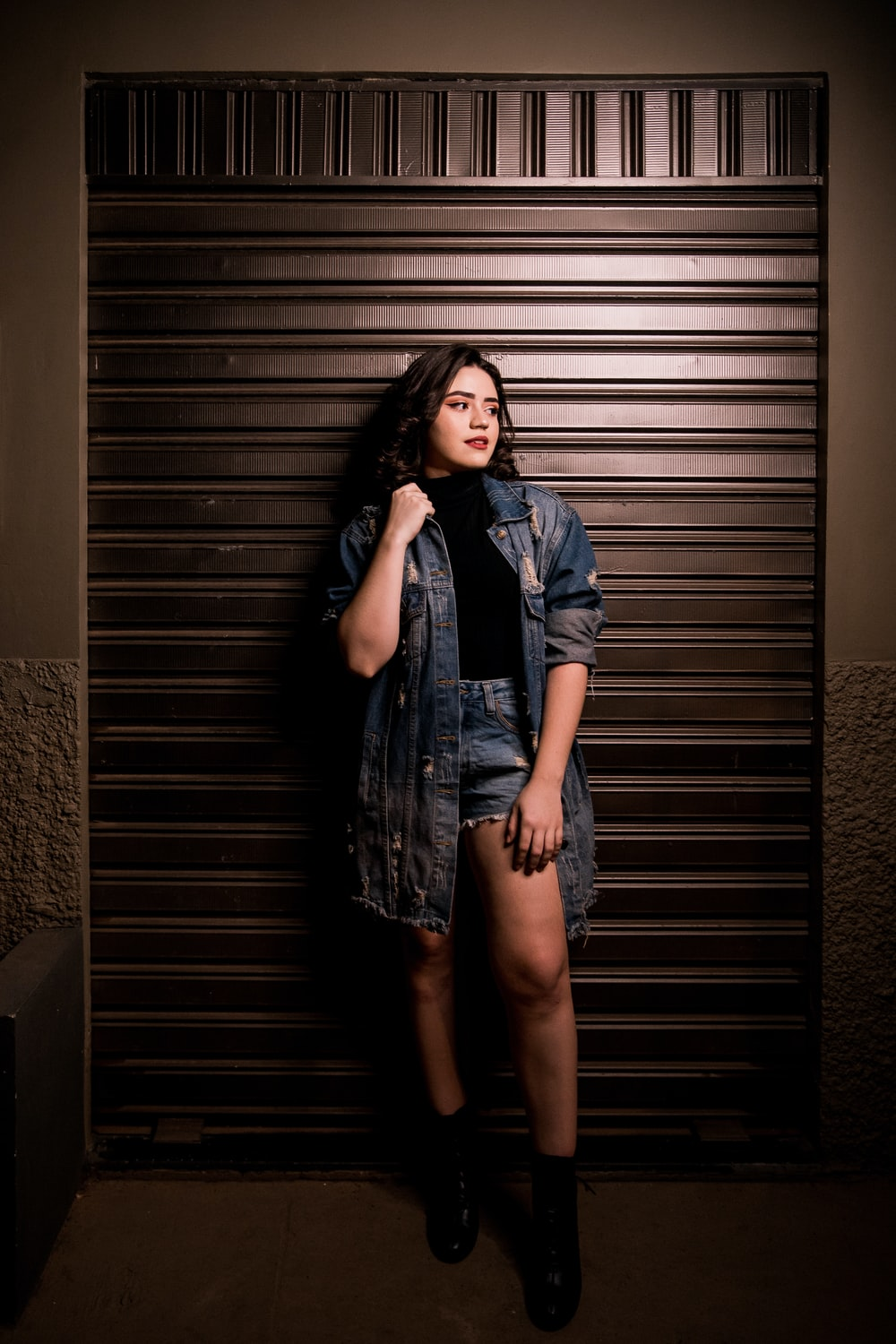 woman in blue denim vest and blue denim button up vest standing beside brown wooden wall