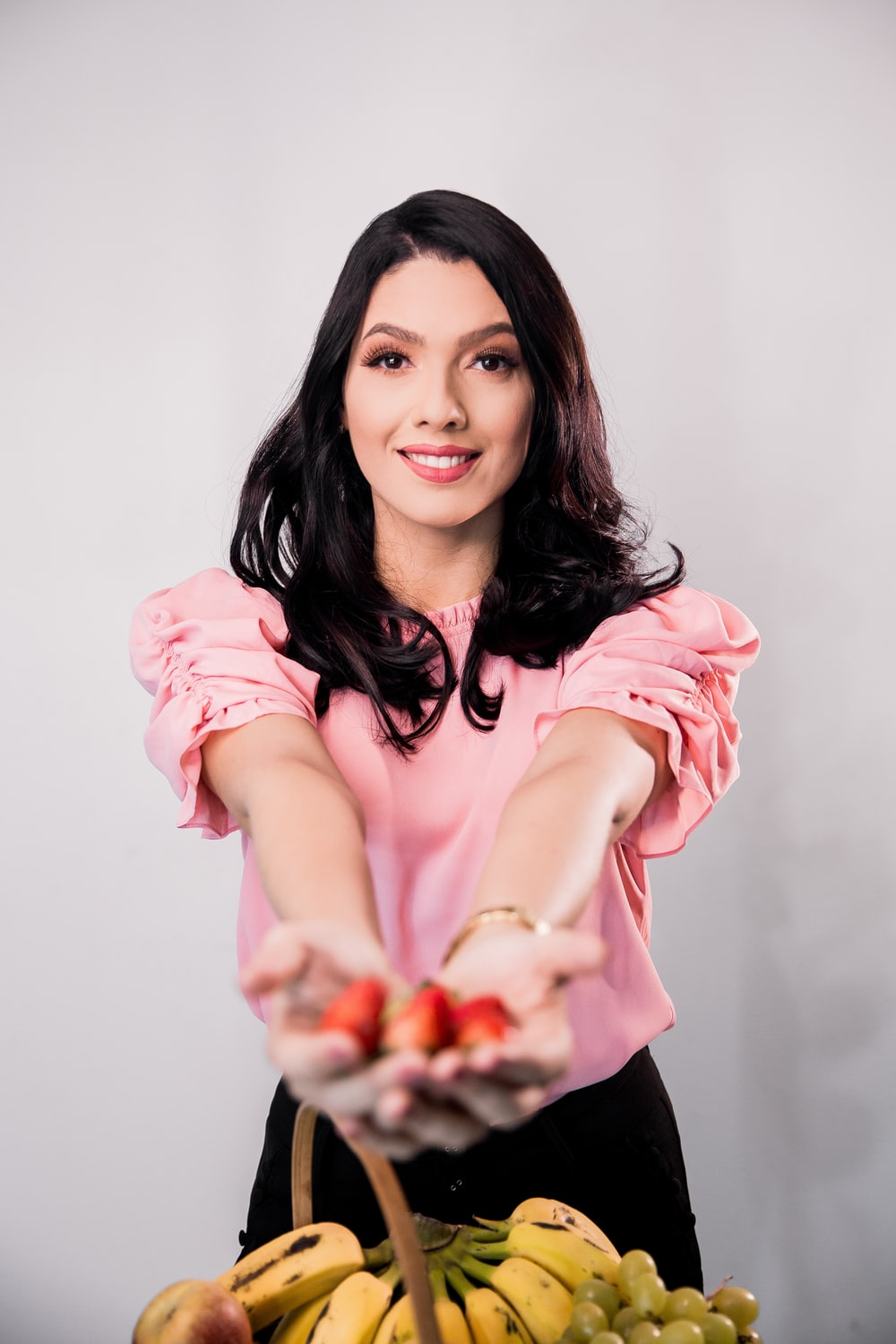 woman in pink long sleeve shirt holding red fruit