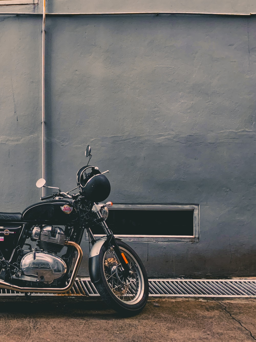 black motorcycle parked beside gray wall
