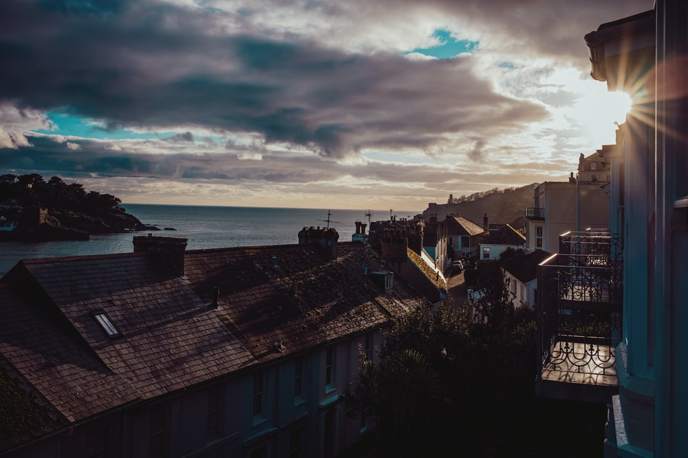 houses near sea under cloudy sky during daytime