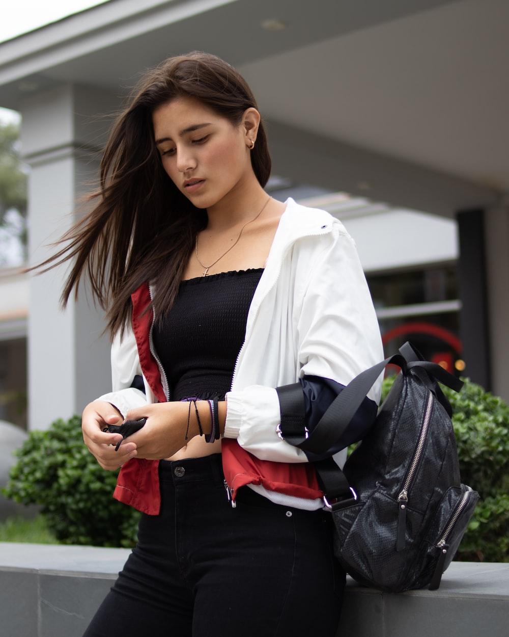 woman in white blazer and black dress shirt holding black leather shoulder bag