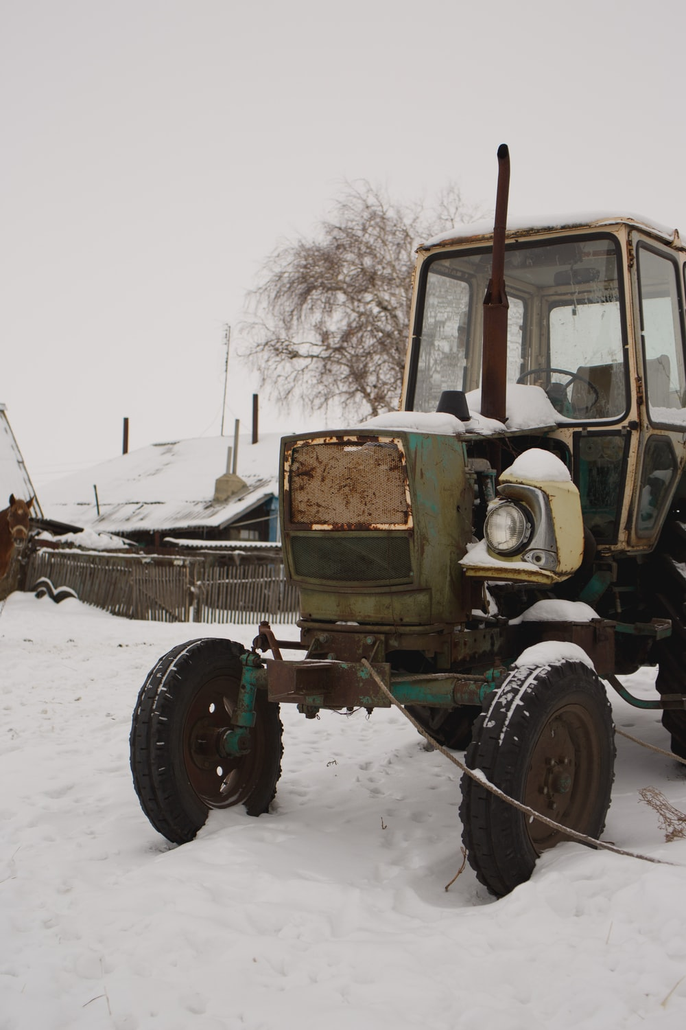 green and brown tractor on snow covered ground during daytime