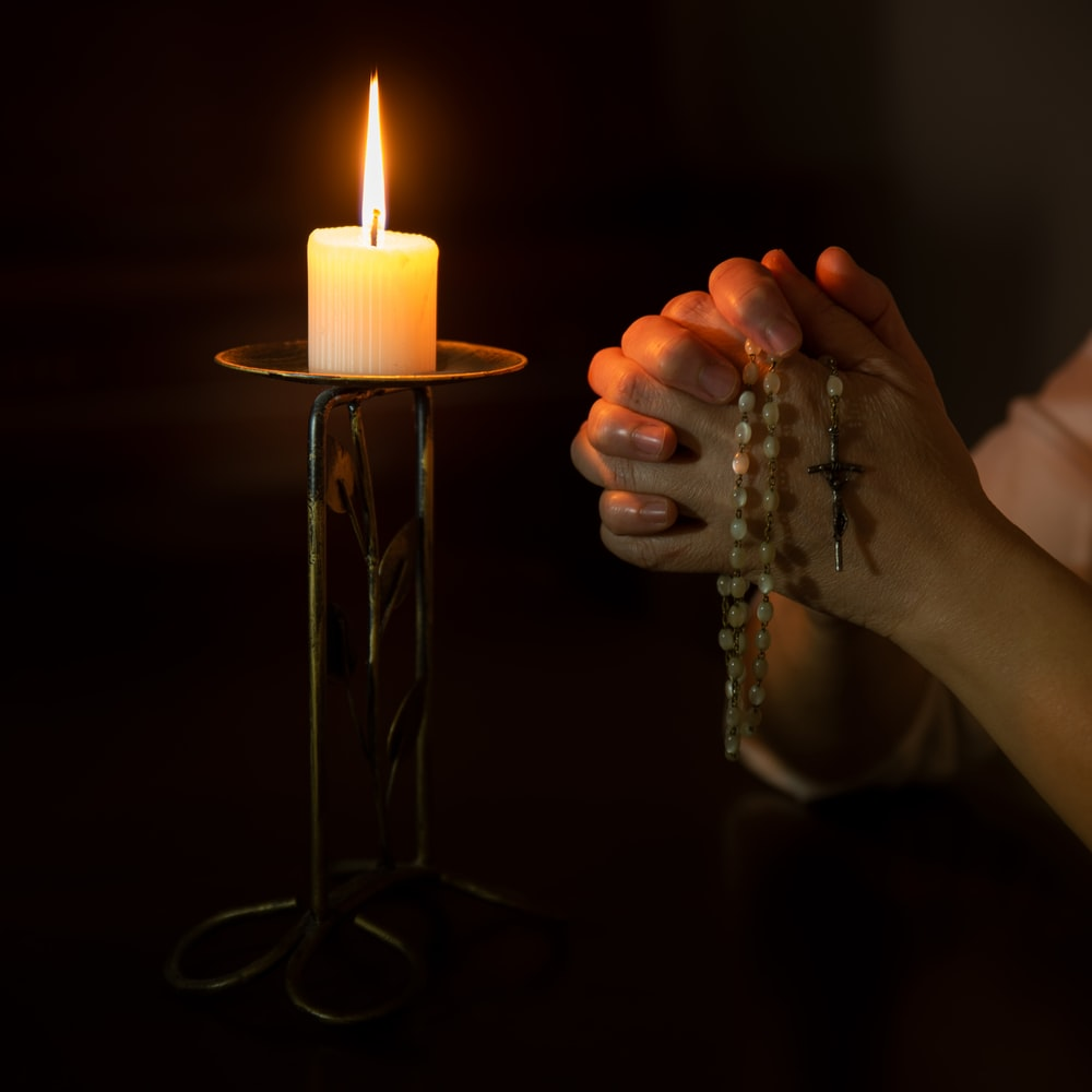 person holding white pillar candle