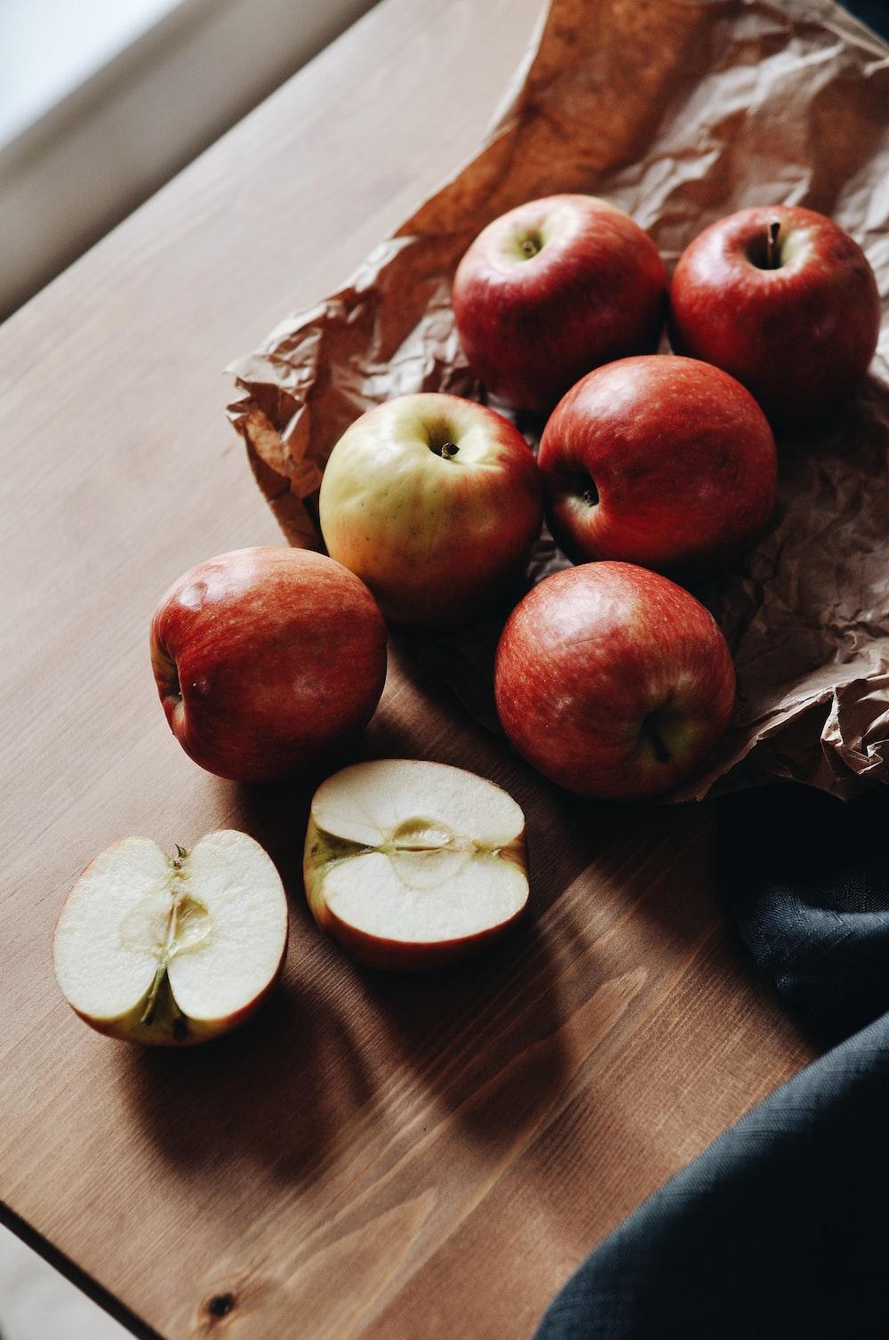 red apples and sliced lemon on brown paper bag