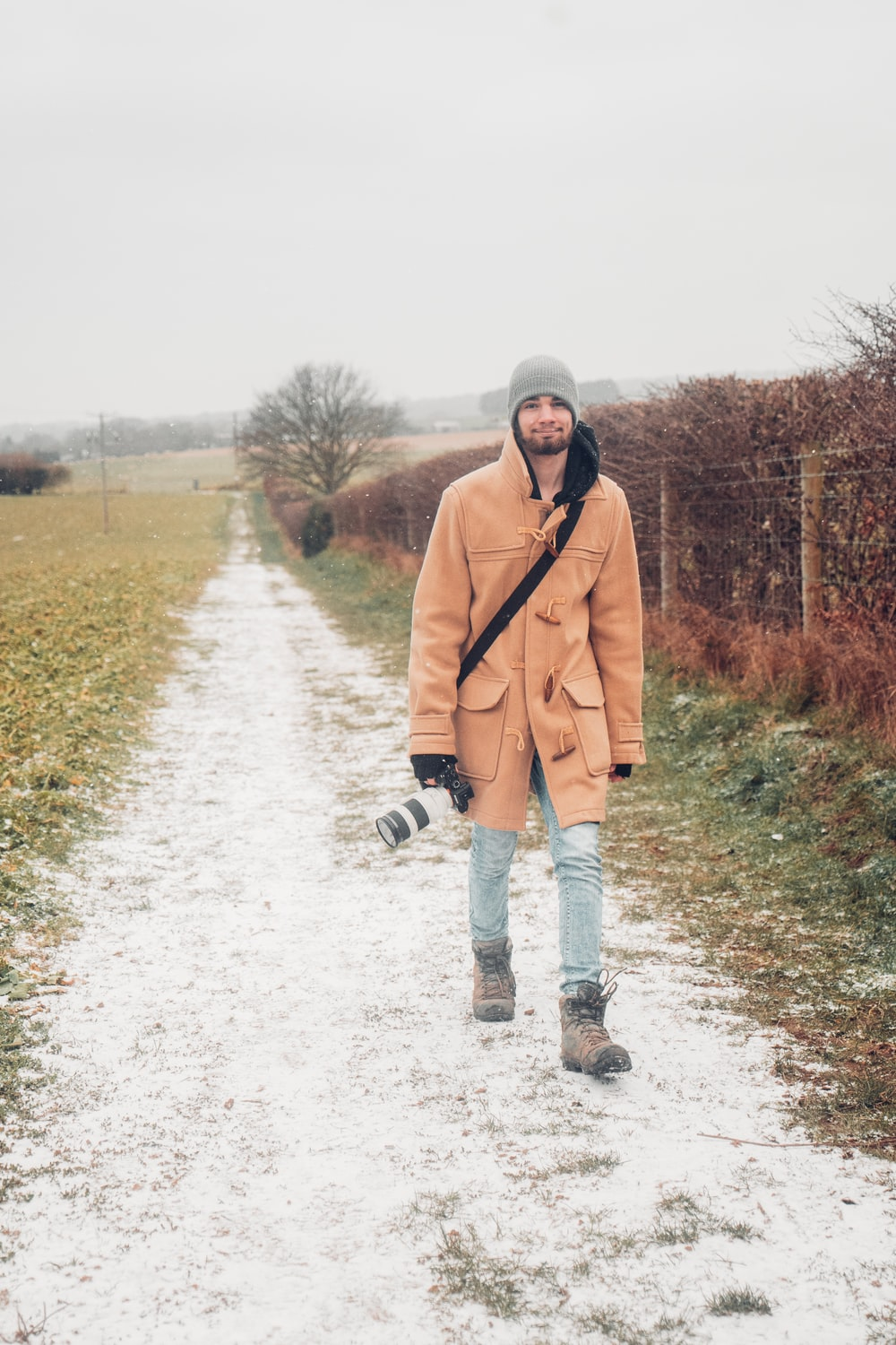 man in brown coat and black pants walking on snow covered ground during daytime