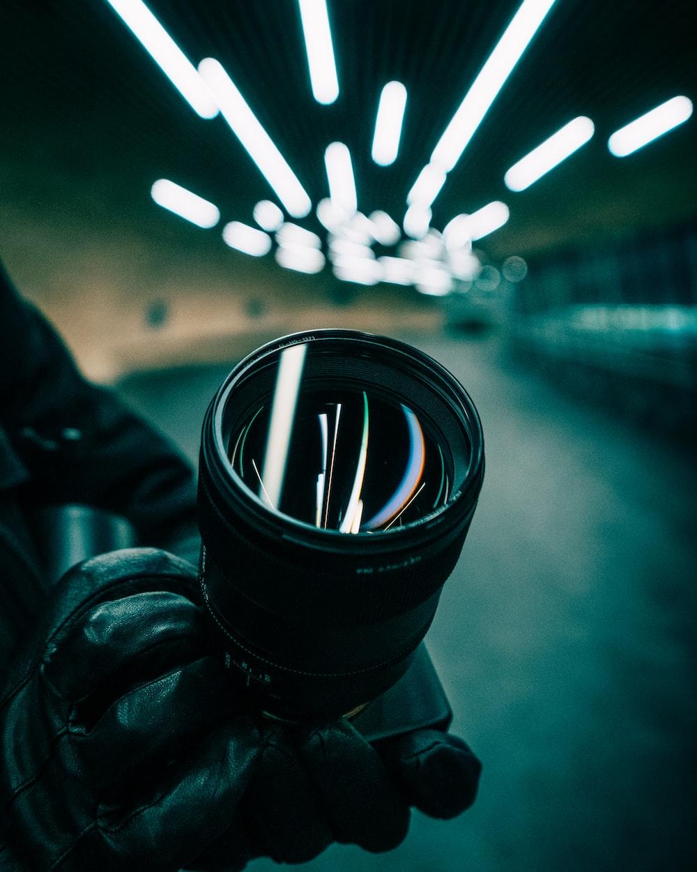 black dslr camera lens on persons hand