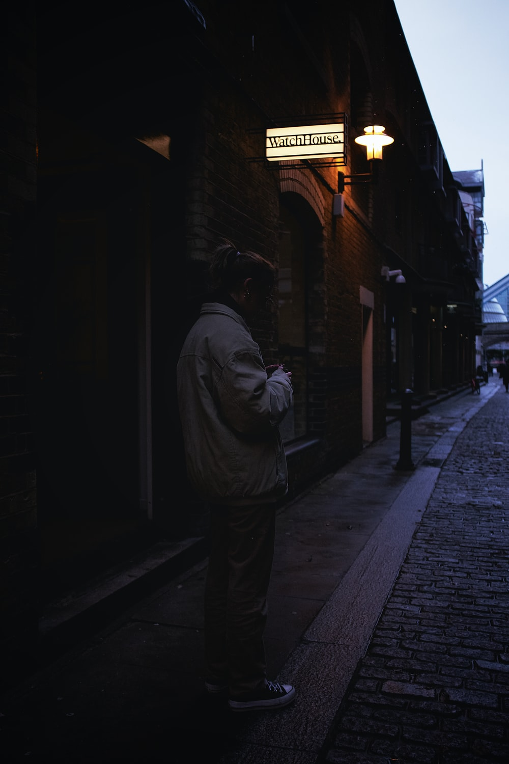 man in gray jacket standing on sidewalk during night time