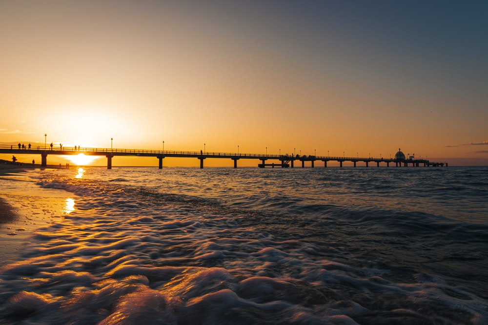 silhouette of bridge over body of water during sunset