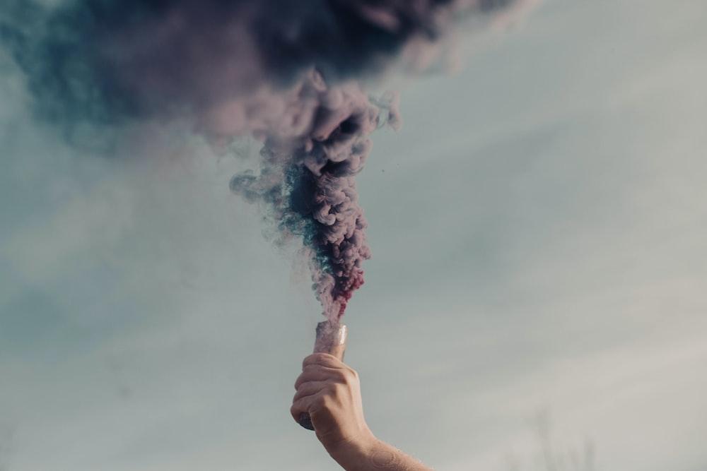 person holding white smoke during daytime