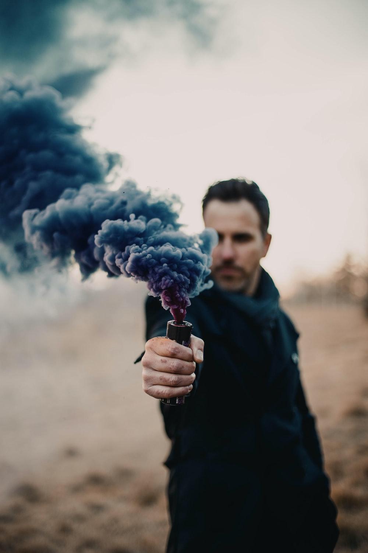 man in black jacket holding blue smoke
