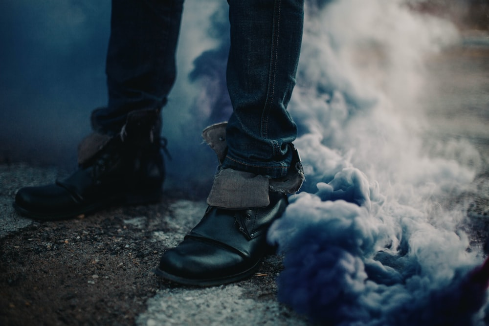 person in blue denim jeans and black leather boots standing on gray sand