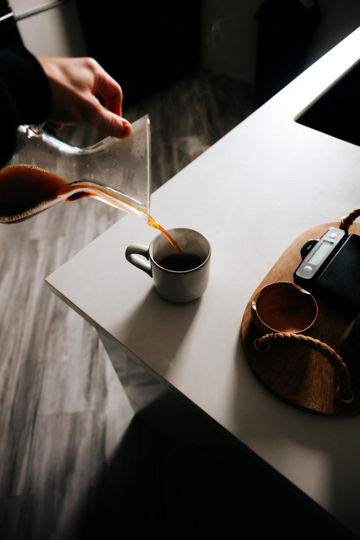 black and white ceramic mug on white wooden table