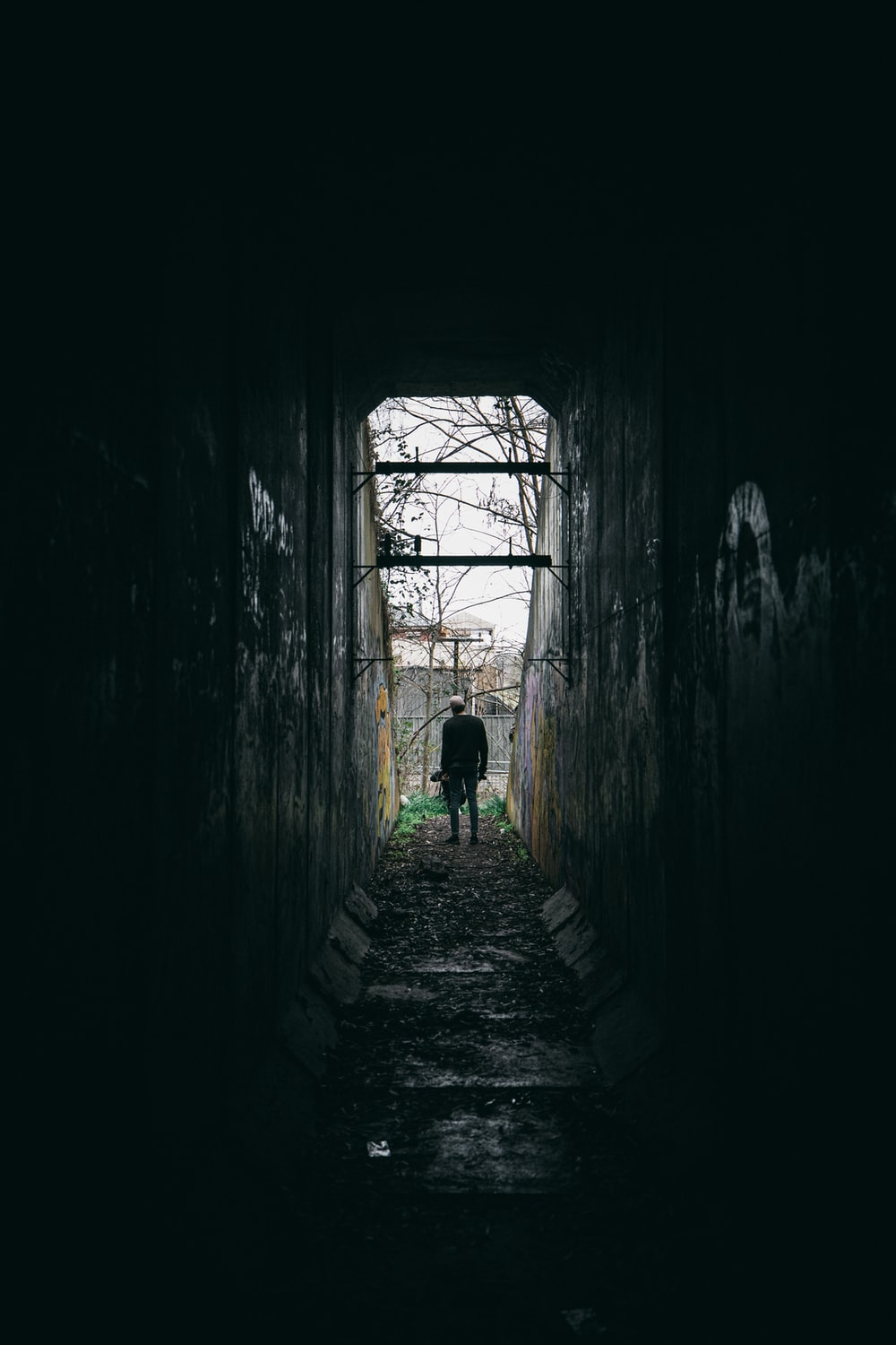 person in green shirt walking on tunnel