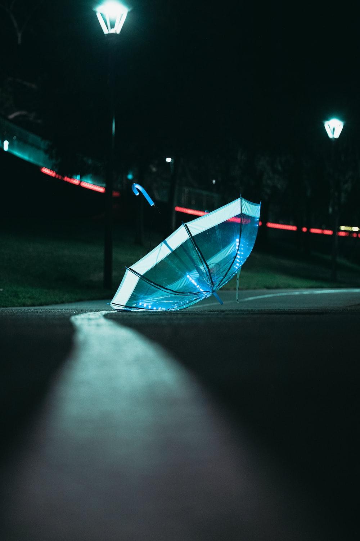blue umbrella on gray asphalt road during night time