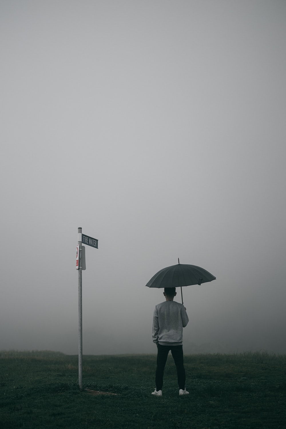 person in white jacket and gray pants holding umbrella standing on foggy field