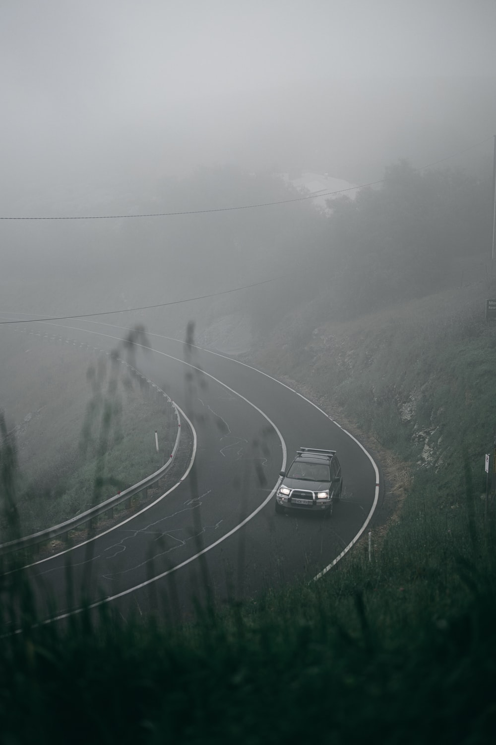 cars on road between green grass field during foggy weather