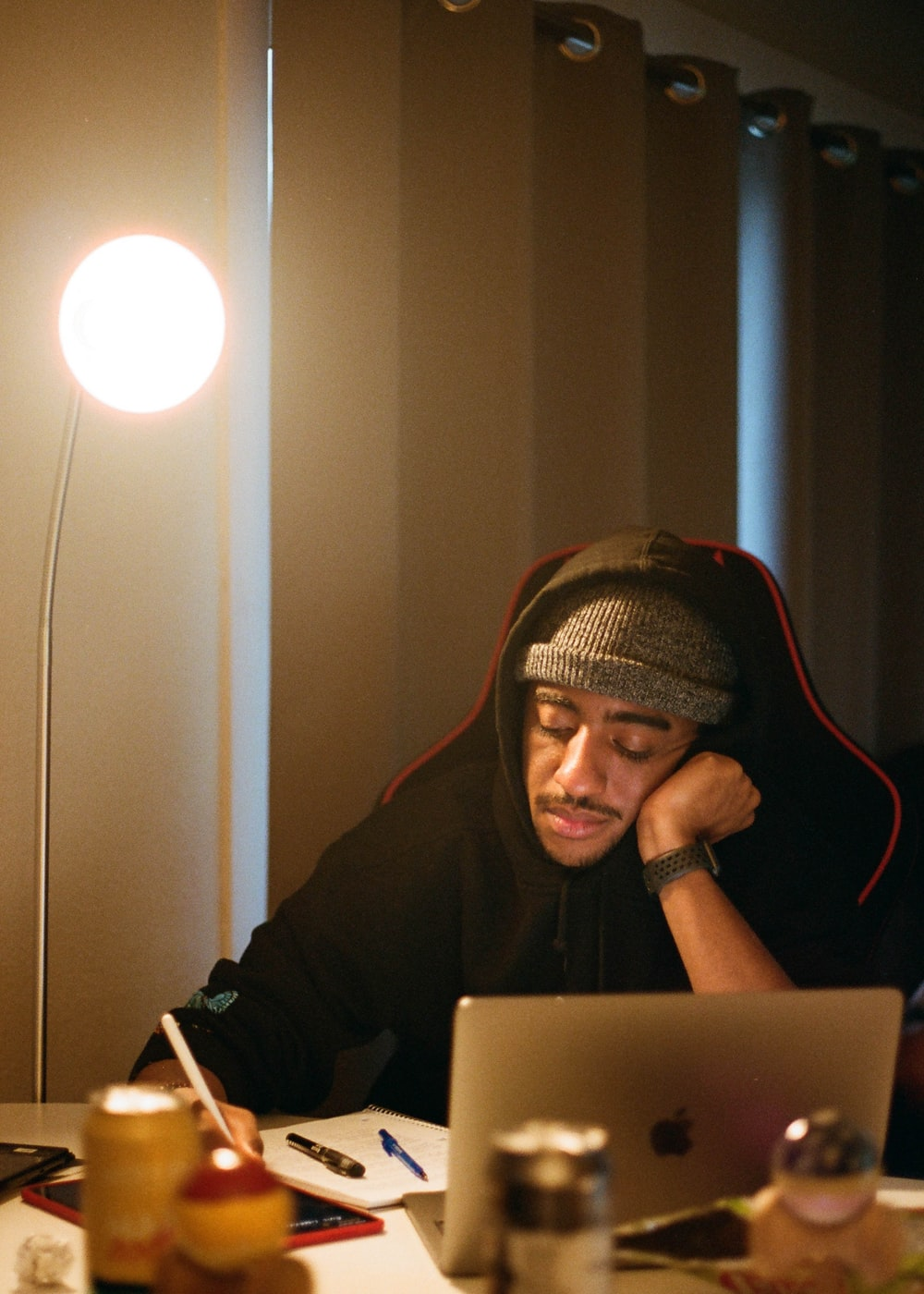 man in black hoodie using macbook