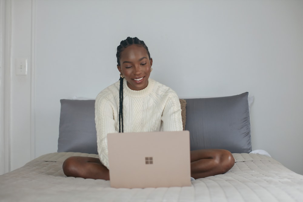 person in white shirt sitting on bed using Surface device