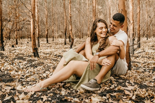 man and woman sitting on ground with dried leaves