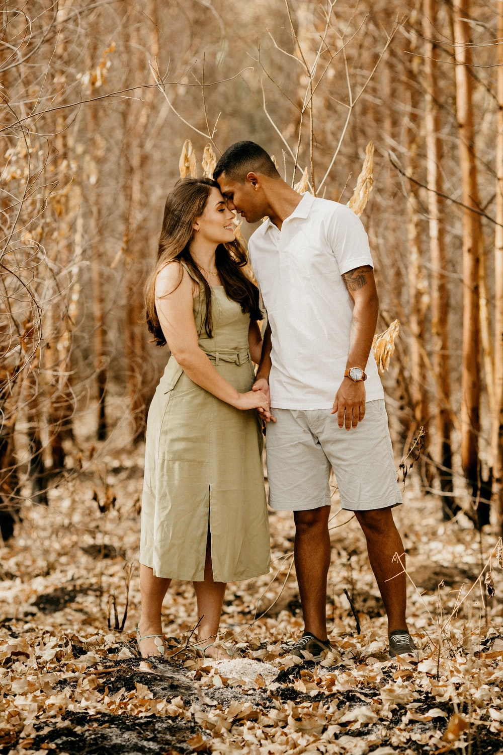 man and woman kissing on the woods during daytime