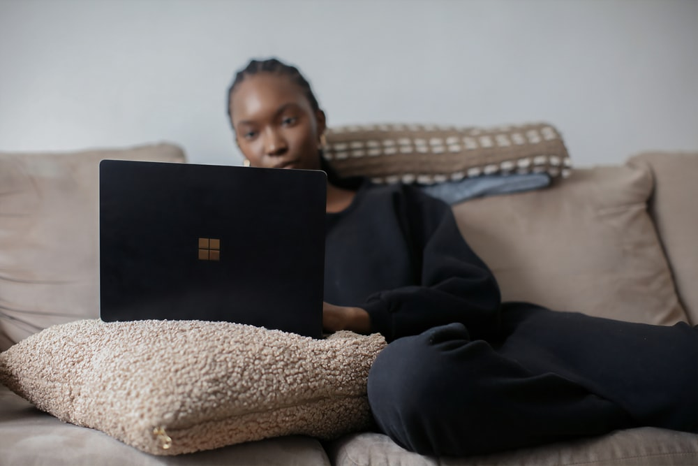 person sitting on couch using black Surface device