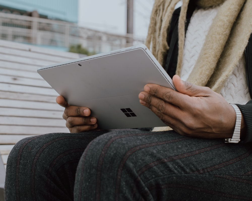 person in gray denim jeans holding Surface device