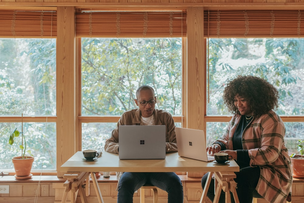 two people sitting on chair in front of Surface devices