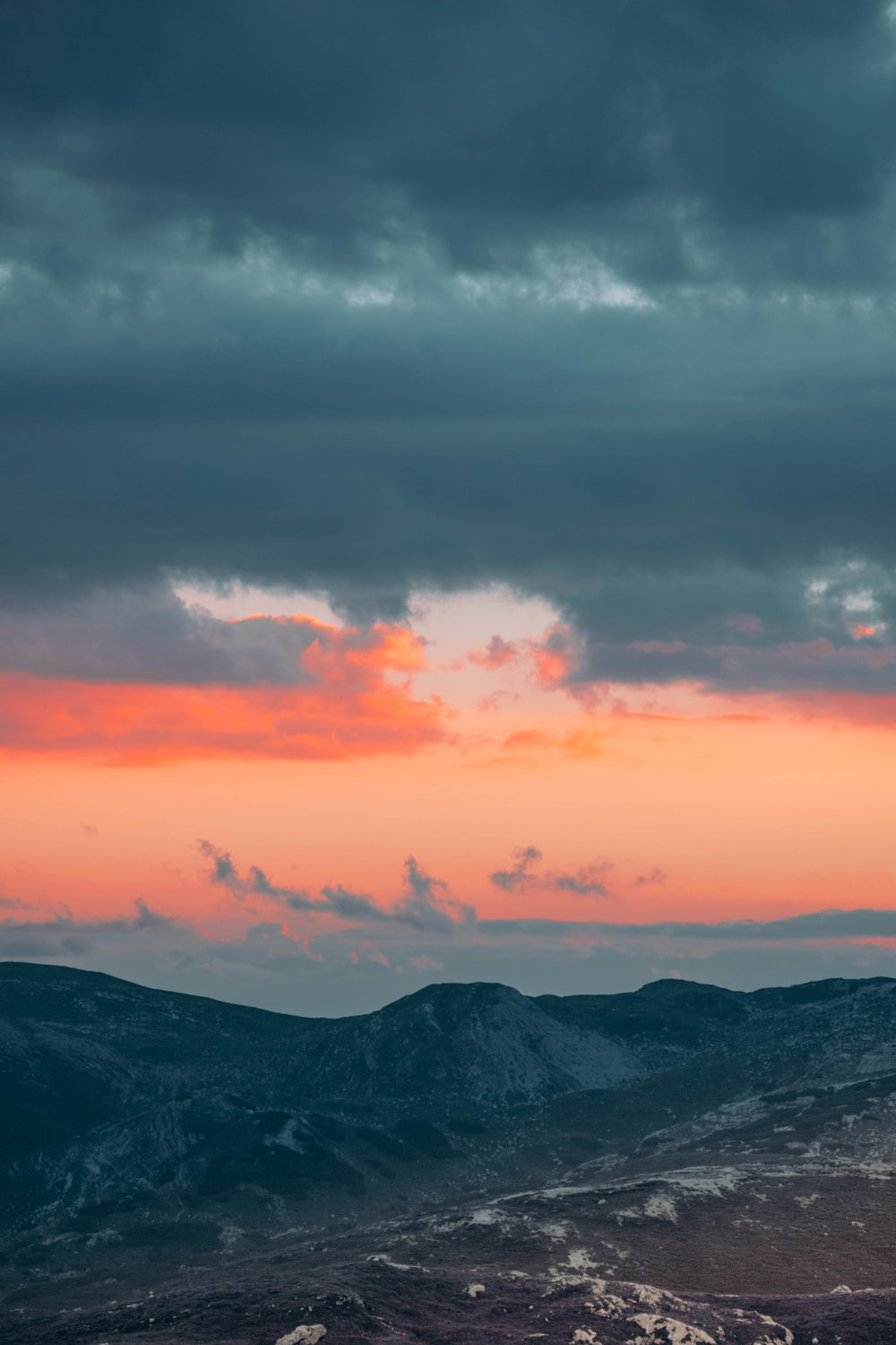 black mountains under orange and gray clouds