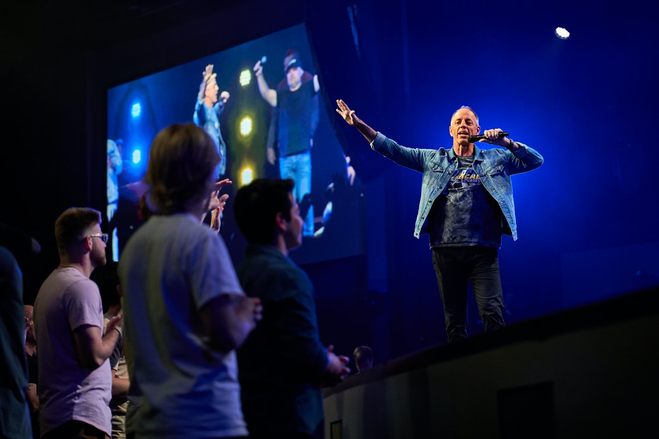 man on a stage singing with a video screen behind him and a crowd looking on