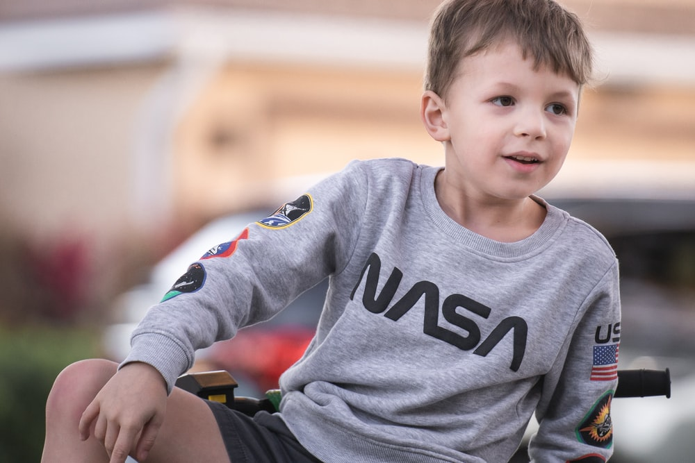 boy in gray crew neck long sleeve shirt sitting on green and black wheelchair