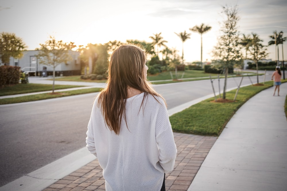 woman in white sweater standing on sidewalk during daytime