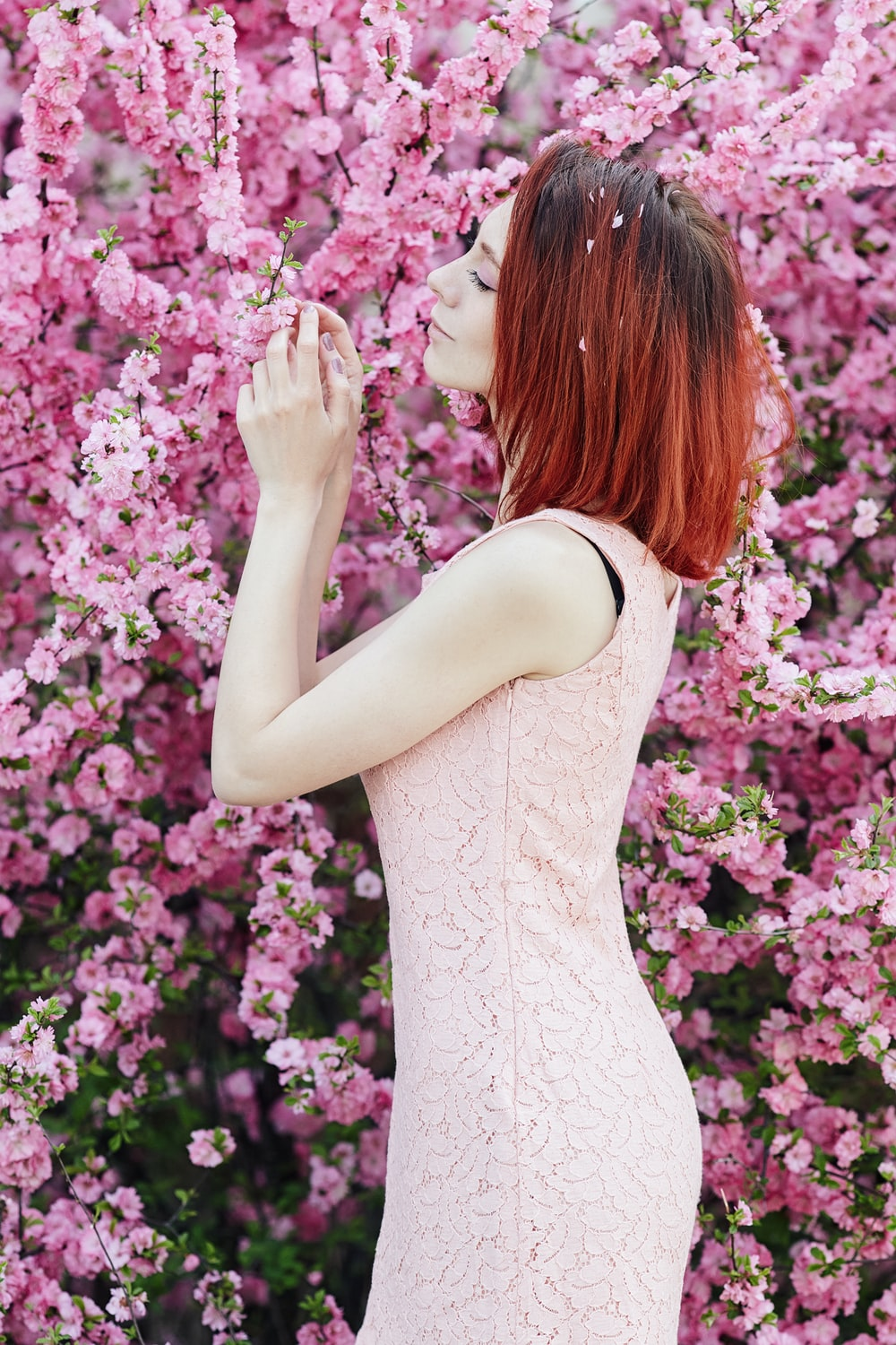 woman in white sleeveless dress standing on pink flower field during daytime