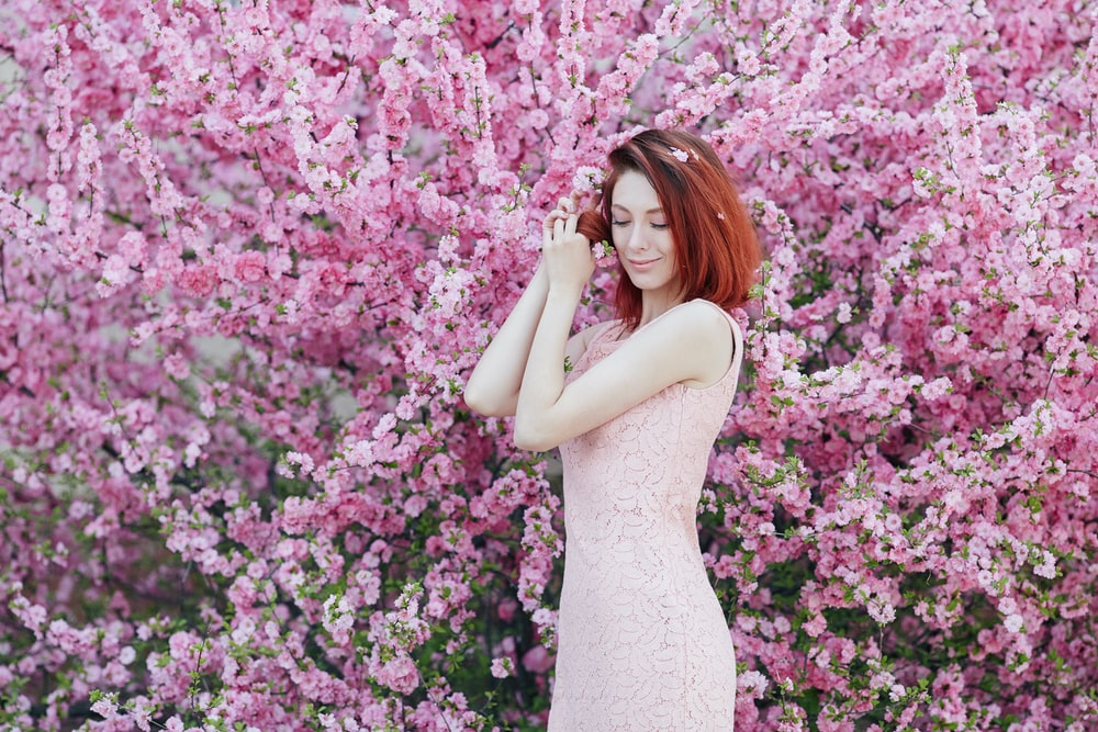 woman in white sleeveless dress standing beside pink flowers