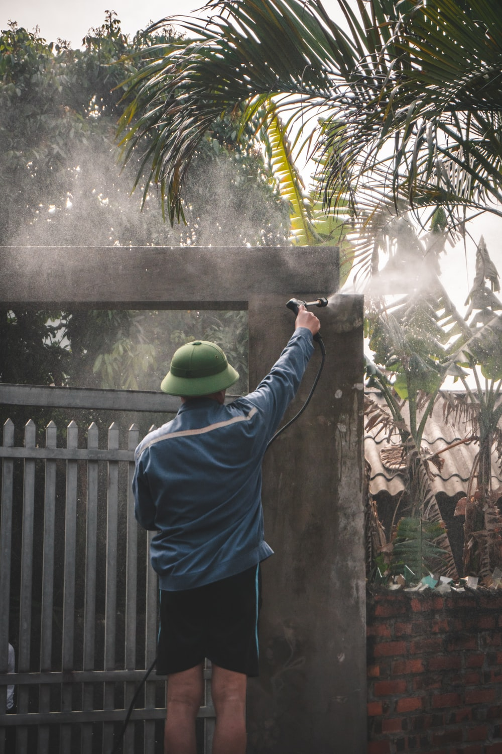 man in blue shirt and blue pants standing near green palm tree during daytime
