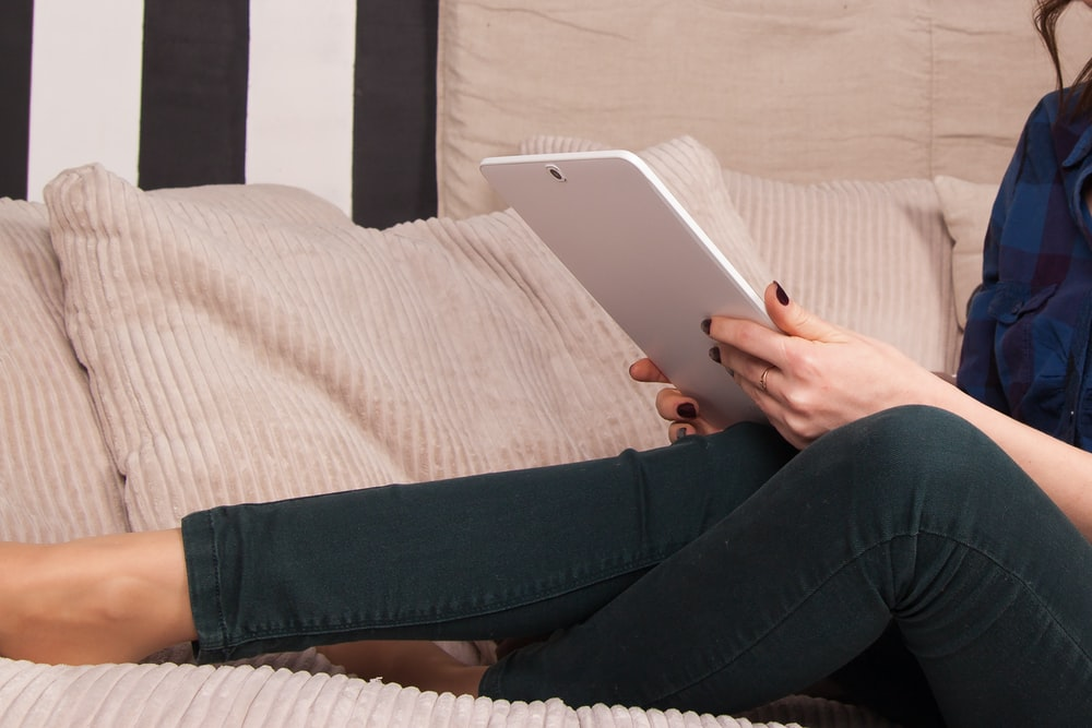 person in white shirt and black pants holding white ipad