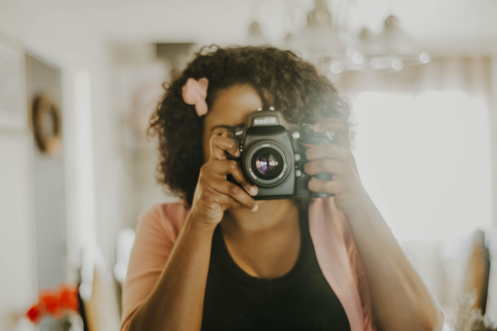 woman in black tank top holding black nikon dslr camera